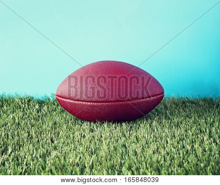 Vintage football over grass and blue background