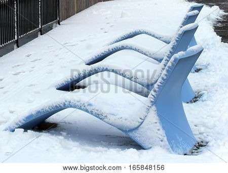 blue resin lounge chairs covered in icy snow