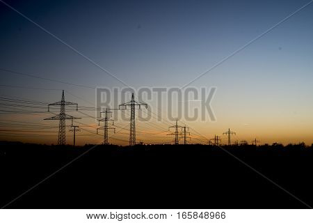 Electric power lines steel tower in landscape sunset sunrise dawn silhouette