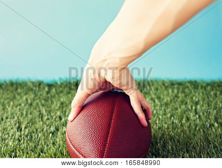 Vintage football over grass being held prior to snap