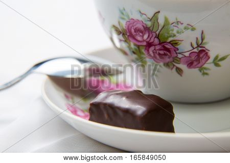 Candy on the saucer next to a cup of tea.