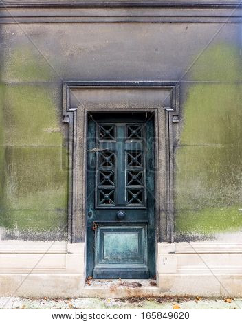 Old closed blue iron door - it is the entrance to an ancient tomb / crypt. A big christian cross decorates the center of it. The ornate rectangle door frame is decorated by a chiseled relief.