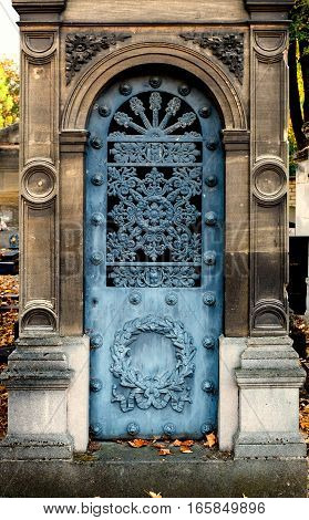 Old blue iron entrance door of a tomb / crypt. It has a round arch and is ornate with chiseled decorations on the stone frame (wreath, flowers and circles).