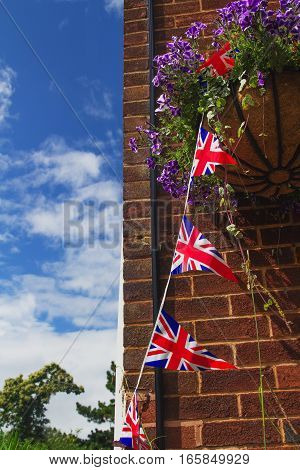 British flags are hanging on a rope. Brick wall. Flowers in pots.