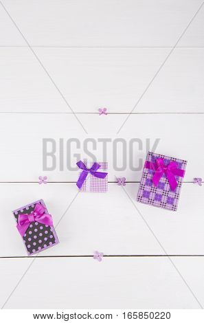 Three purple gift boxes surrounded by lilac flowers on white background.