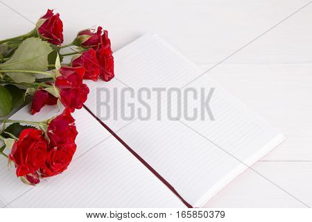 Bouquet Of Red Roses With Open Notebook On White Background