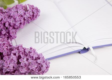 Bouquet Of Lilac With Open Notebook On White Background