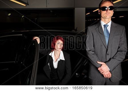 bodyguard standing in front of a black limousine, protecting the godfather's daughter or a famous actress as she is getting out