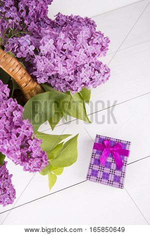 Bouquet Of Lilac In Wicker Basket With Purple Gift Box On White Background