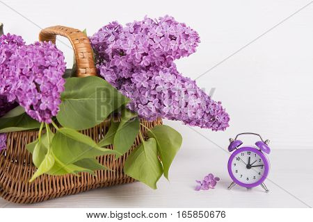 Bouquet Of Lilac In Wicker Basket With Purple Alarm Clock On White Background