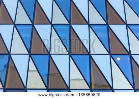 Colorful fasade made of triangles of different colors orange blue and white