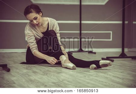 Pretty Young Graceful Ballet Dancer Warms Up In Ballet Class. Ballerina Putting On Pointes