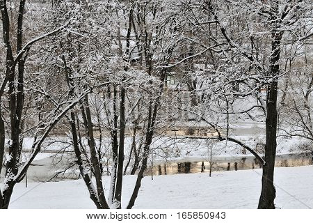 Trees covered with snow are reflected in the calm waters of a lowland river, Pakhra river, Podolsk, Moscow region, Russia