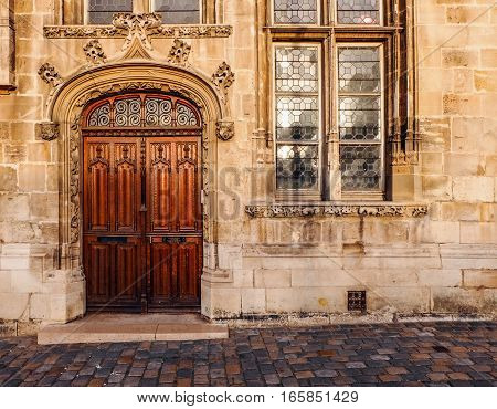 Wooden double door entry of an old church. The door frame has a rounded arch and is beautifully ornate with floral ornaments. The carved reliefs in the stone can also be seen below the glass window besides the door.