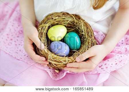 Cute Little Girl Holding A Nest With Colored Easter Eggs At Home On Easter Day