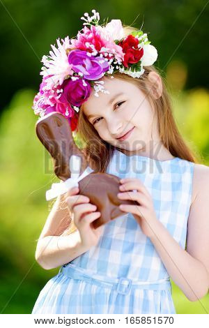 Cute Little Girl Wearing Flower Wreath Eating Chocolate Easter Rabbit