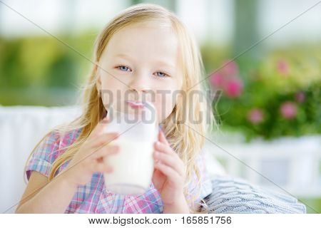 Cute Little Girl Drinking Fresh Organic Milk At Sunny Summer Day