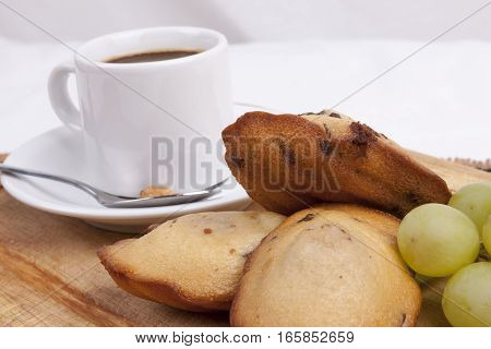 chocolate chip madeleine and coffee on a wooden board