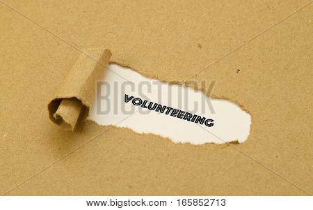 Volunteering word written under brown torn paper.