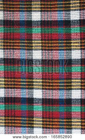 Woven color decorative squares tartan cloth as background closeup vertical view
