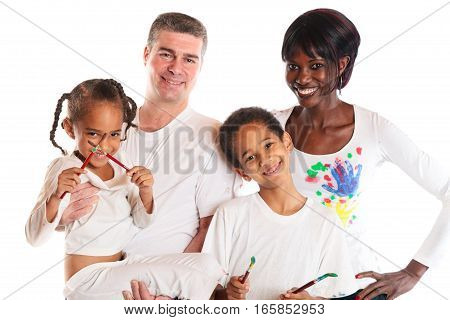 studio shot of african mother, european father and their children painting.