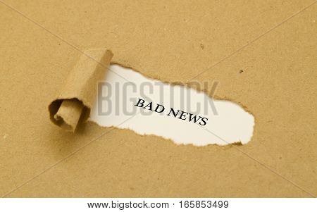 Bad news  word written under torn paper .