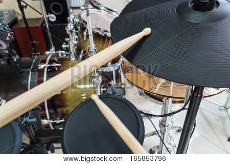 Two drumsticks on black electronic drum in music studio