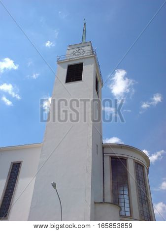 Photo of a modern Christian church in front of a blue sky