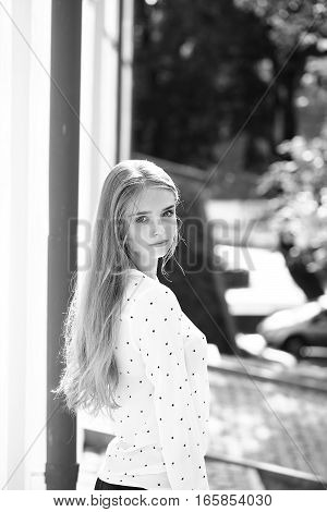 Pretty cute woman or girl with beautiful long hair in pants and blouse outdoor on sunny day black and white
