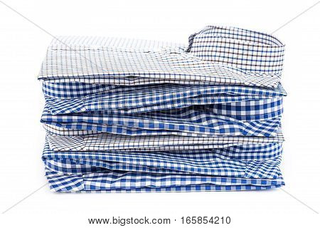 Side view of stack of folded men's classic cotton plaid shirts with long sleeve isolated on white background.