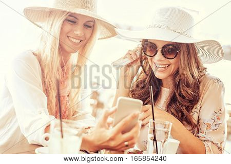 Two young women drinking coffee and listening to music in cafe.