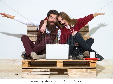 Young happy couple spend time together on wooden pallet sofa. Handsome man bearded hipster with beard uses laptop computer. Pretty girl or beautiful woman reads book