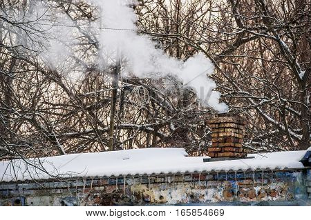 Close-up many smoke from brick chimney in winter