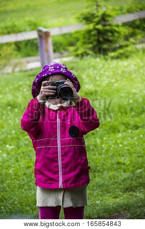 little girl shooting with big photo camera