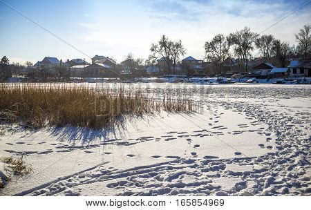 winter landscape of frozen river with many human footprints