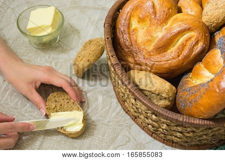 Woman spread the butter on the slice of bread and different bread in the wicker basket