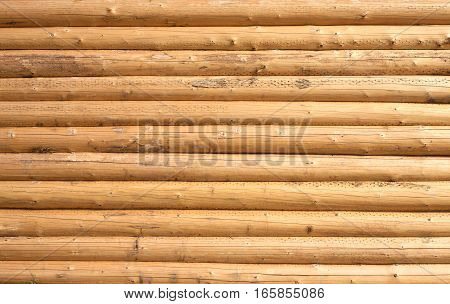 Wall of a house from planed horizontal logs as background closeup