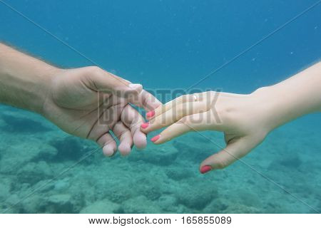 Male And Female Hands Under Water.