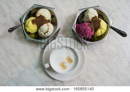 Two metal bowl with fruit ice cream and one cup of coffee on the gray table