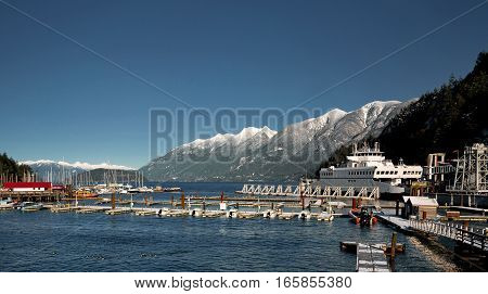 Horseshoe Bay West Vancouver Ferry Terminal and Marina, parking of boats and yachts on the background of snow-covered mountains ridge