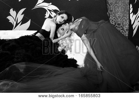 two pretty women in elegant evening dresses with long veil skirts in jewellery earrings with gem stones in room black and white