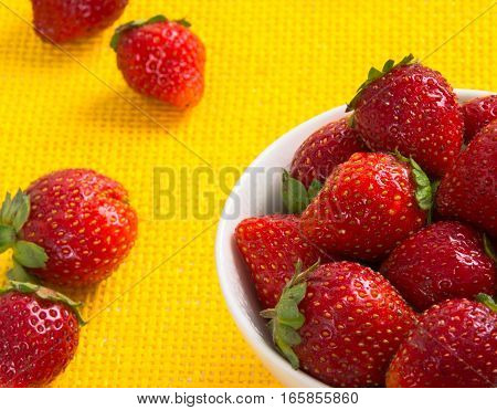 strawberry in a white cup against the background of a yellow cloth