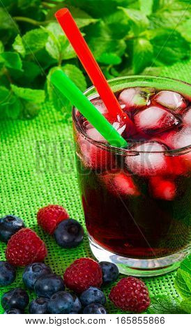 berry juice with ice against the background of a green cloth