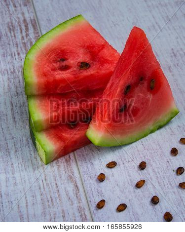 pieces of watermelon on a white wooden table