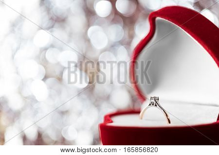 wedding diamond ring in  red heart shaped gift box on background with bokeh. Valentine's day