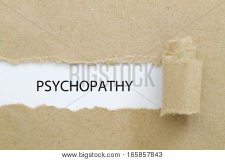 psychopathy word written under torn paper .