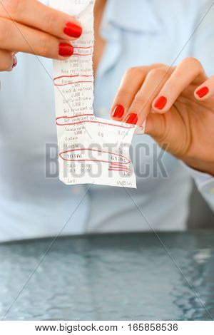 Daily expenses concept with woman tossing a paper fiscal receipt - Plastic Bag, Ecotax and Shower gel are the words from the paper