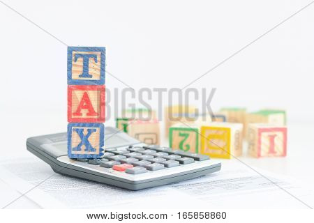 Taxation concept with wooden cubes and pocket calculator