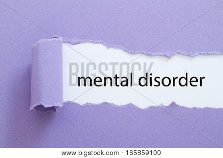 mental disorder word written under torn paper.