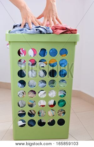 Laundry basket full to the brim with dirty clothes